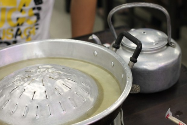 Moo Kata pan/stove filled with a clear broth.